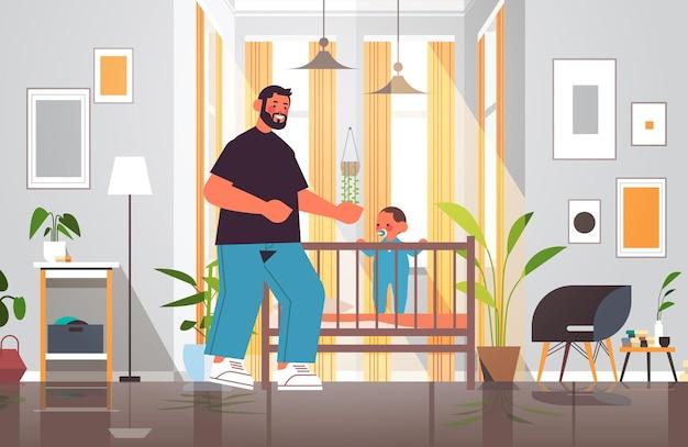 ベビーベッドの父性の子育ての概念で幼い息子と遊ぶ若い父親は、自宅の寝室のインテリアの完全な長さの水平方向のベクトル図で彼の子供と一緒に時間を過ごすお父さん