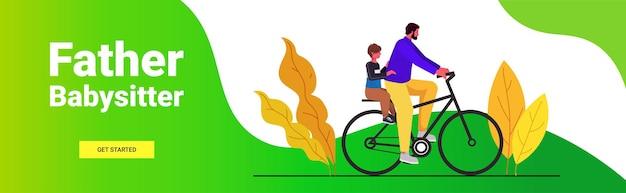 幼い息子と一緒に自転車に乗る若い父親は、父親の概念のお父さんが彼の子供の風景の背景と水平に時間を過ごす