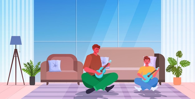Young father teaching little son to play guitar parenting fatherhood concept dad spending time with his kid living room interior full length horizontal