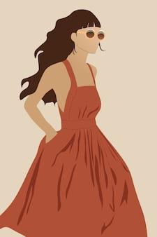 暗いオレンジ色のドレスと歩いて丸いサングラスの若い女性モデル