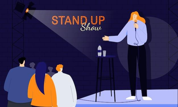 若い女性のスタンダップコメディアンは、ショーの冒頭で聴衆に挨拶し、マイクを介して人々に直接話します。ユーモラスな物語のジョークとワンライナーのモノローグ