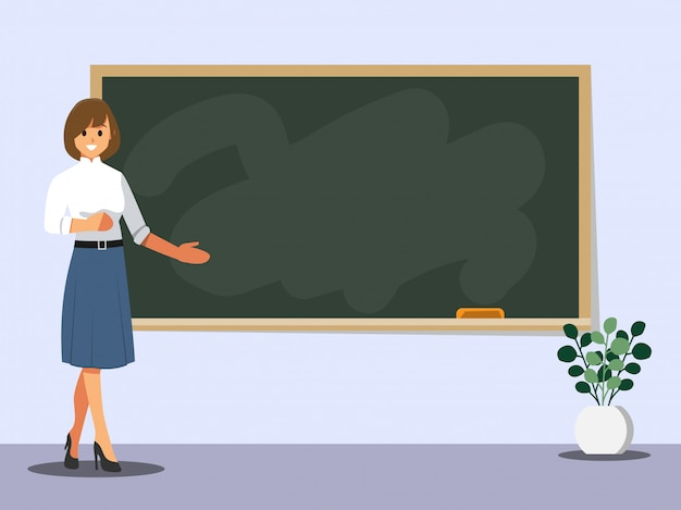 Young female teacher on lesson at blackboard in classroom