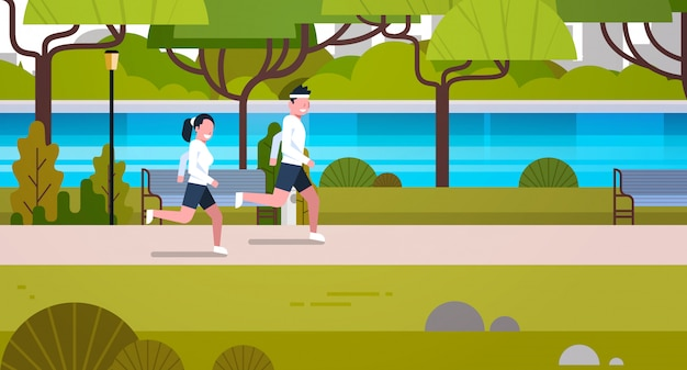 Young fit couple jogging outdoors in modern public park sport activities