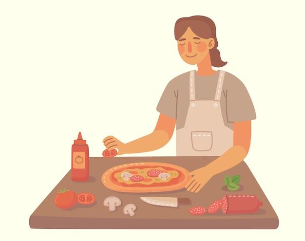 自宅のキッチンでピザを調理する少女。