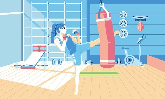 Молодая девушка делает упражнения по кикбоксингу в тренажерном зале со многими тренажерами