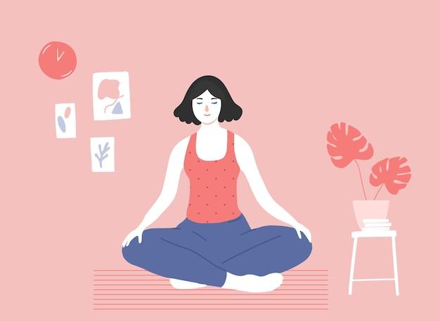 Молодая девушка делает медитацию, сидя в позе скрещенных ног на полу в уютной розовой комнате осознанность