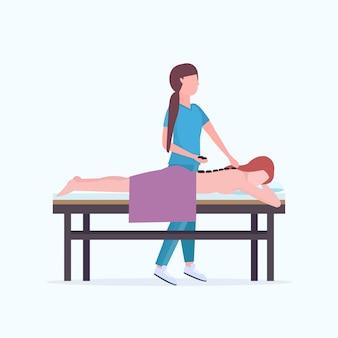 Молодая девушка, имеющая массажистка массаж спины горячими камнями в униформе массаж пациента тело женщина расслабляющий лежа на кровати роскошь спа салон процедуры концепция полная длина