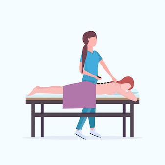 Young girl having hot stone back massage masseuse in uniform massaging patient body woman relaxing lying on bed luxury spa salon treatments concept full length
