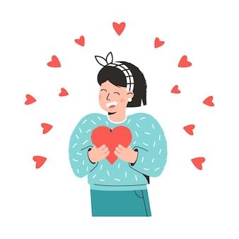 Молодая девушка держит сердце в руках и смеется концепции счастливого дня святого валентина