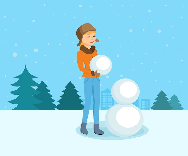 Молодая девушка в зимней одежде в парке лепит снеговика.