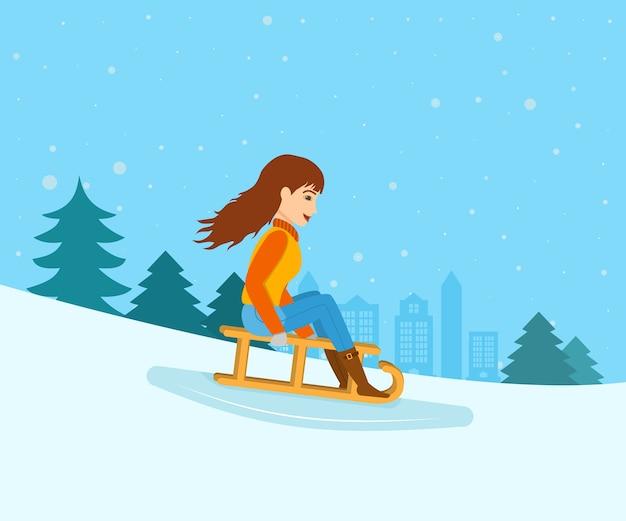 Молодая девушка в зимней одежде, скатилась со склона горы на санках.