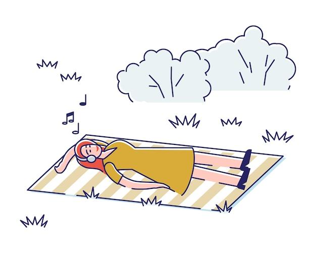 Молодая девушка слушает музыку, лежа на одеяле в парке.