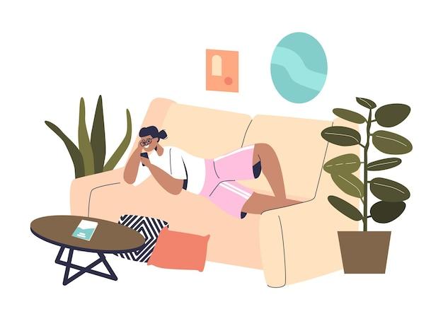 스마트폰 장치를 사용하여 집에서 소파에 누워 있는 어린 소녀는 소셜 미디어에서 친구들과 문자 메시지를 편안하게 보냅니다.