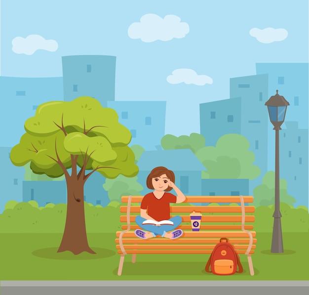 Молодая девушка, читающая книгу, сидя на скамейке в парке