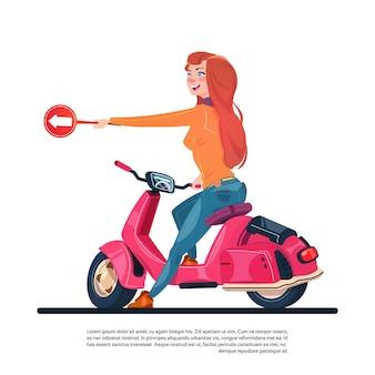 Молодая девушка езда электрический скутер держать дорожный знак со стрелкой