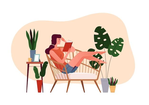 若い女の子は肘掛け椅子に座って本を読む