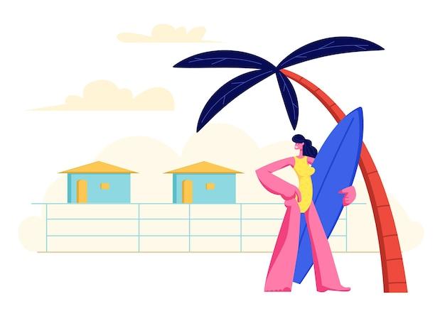 Молодая девушка с доской для серфинга в руках, стоя на песчаном пляже под пальмой на фоне курортных домиков