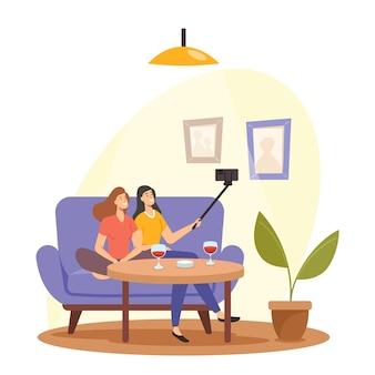 リラックスして、ソファに座ってワインを飲みながらスマートフォンで自分撮りをする若い女の子。女性ホームパーティー、ガールフレンドミーティング