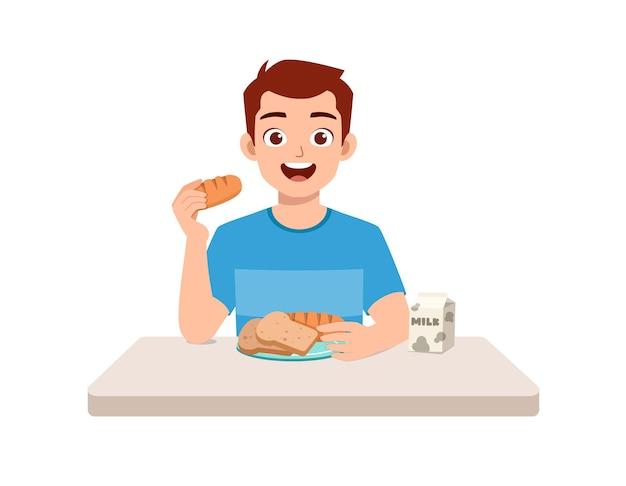 若い格好良い男はパンを食べ、ミクを飲む