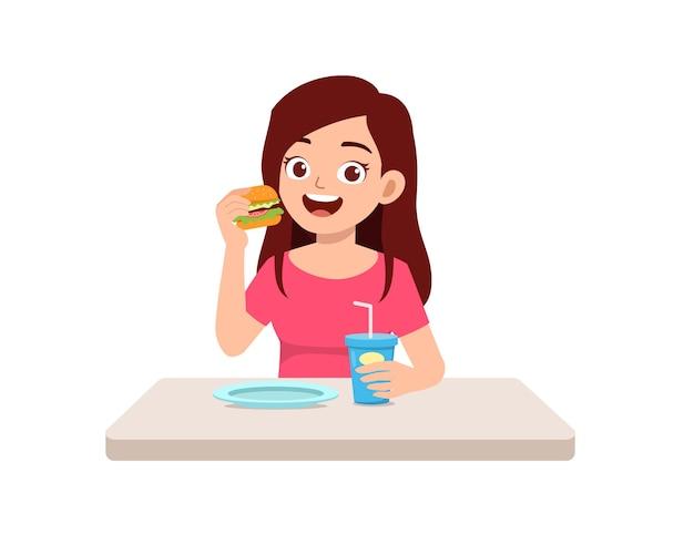 젊은 잘 생긴 여자는 건강에 해로운 패스트 푸드를 먹는다