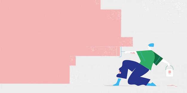 Молодой парень красит стену краской, валик. скопируйте место для текста на красочной стене