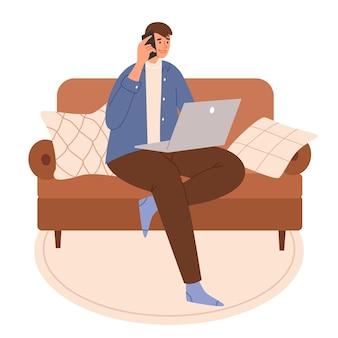 Молодой парень разговаривает по телефону и сидит на диване с ноутбуком