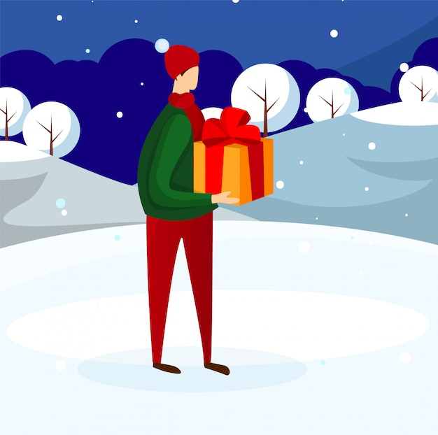 Young guy in winter clothing holding present box.