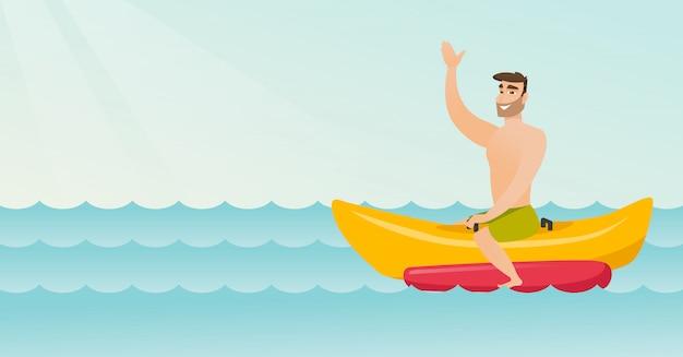Young happy caucasian man riding a banana boat