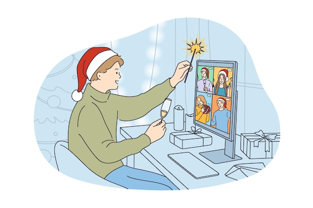 Young happy man in festive hat drinking champagne holding sparkler and chatting with friends online on laptop virtual zoom video celebrating holiday