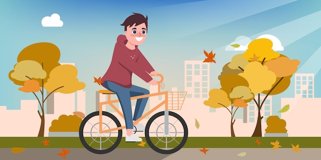 Young happy man ride a bicycle in the autumn