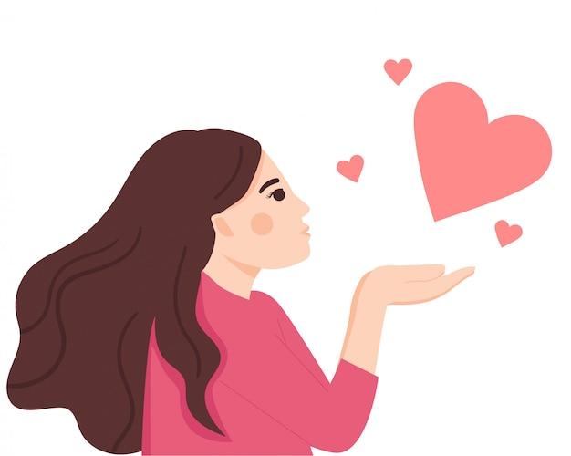 Молодая счастливая женщина, держащая руки, подняла и дует поцелуй. вид сбоку.