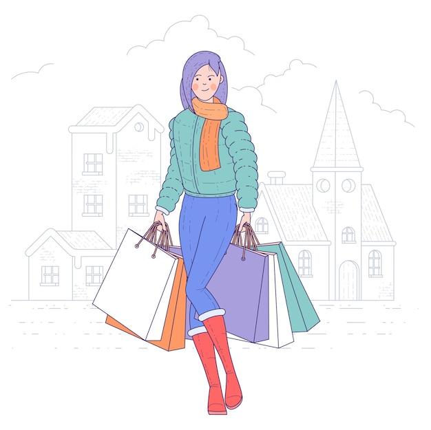 旧市街の都会の背景に買い物袋を保持している若い幸せな女性。