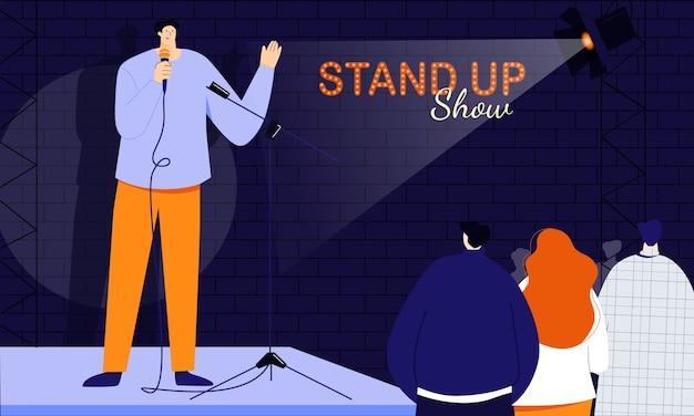 若い男性のスタンダップコメディアンは、ショーの冒頭で聴衆に挨拶し、マイクを介して人々に直接話します。ユーモラスな物語のジョークとワンライナーのモノローグ