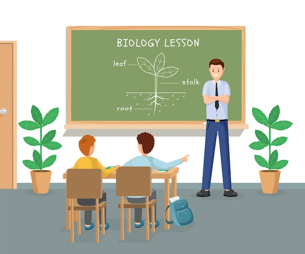 Young male teacher explaining plant structure at chalkboard