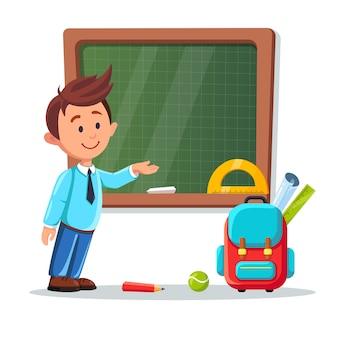 教室の黒板でレッスン中の若い男性教師。学校に戻るレタリング付きの黒板。家庭教師とバックパックは白い背景で隔離。教育教育の概念。