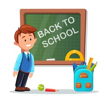 教室で黒板にレッスンの若い男性教師。学校に戻るレタリングが付いている黒板。家庭教師と白い背景のバックパック。教育教育のコンセプトです。