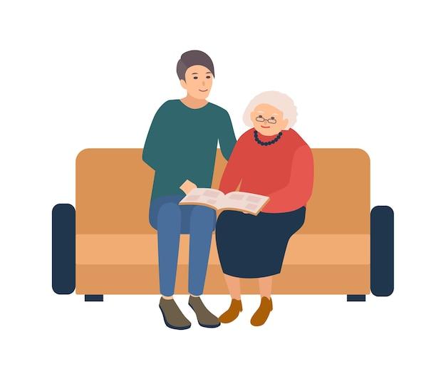 幸せな高齢者の女性が付いているソファーに座っていると写真アルバムの写真を探している若い男性ボランティア