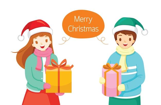 メリークリスマスと言ってギフトボックスを持つ若い男と女