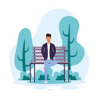 公園の椅子に座っているカジュアルな若い男