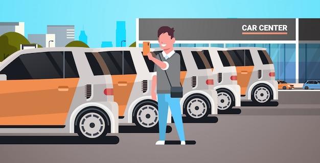 スマートフォンのオンライン自動レンタルサービスを保持しているモバイルアプリケーションのカーシェアリングのコンセプトの男を使用して車のセンターの駐車場で車を選択する若い男