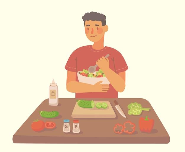 自宅のキッチンで自家製サラダを調理する若い男。材料を使ったサラダの調理。