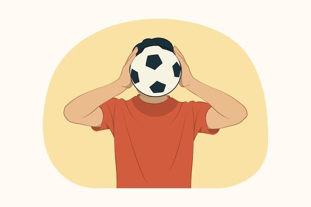 Молодой человек, закрывающий лицо футбольным мячом