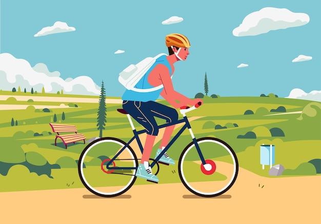 백그라운드에서 아름다운 녹색 풍경과 교외에서 자전거 젊은 남자