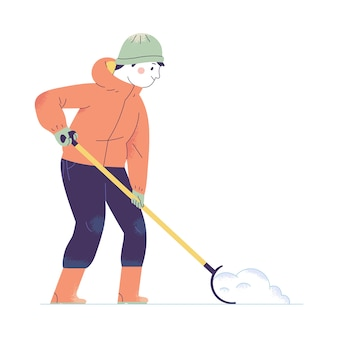A young man dredges snow with a snow shovel in winter