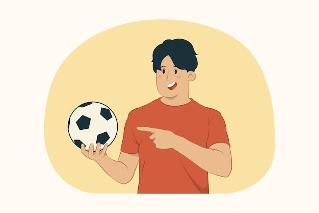 Молодой человек футбольный фанат указывает указательным пальцем на футбольный мяч