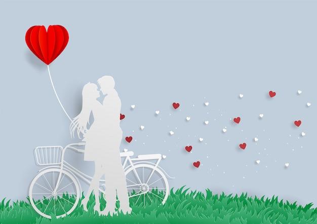 Молодой человек обнимает свою возлюбленную с велосипедом и красным сердечным воздушным шаром на зеленой траве, чувствуя счастливую любовь