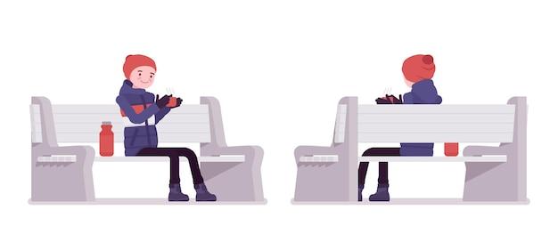 魔法瓶とベンチに座っている縞模様のダウンジャケットの若い男