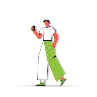 スマートフォンのカメラの男性の漫画のキャラクターでselfie写真を撮るカジュアルな服装の若い男