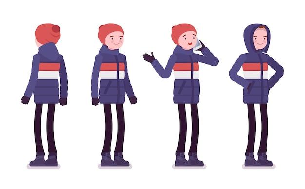 Молодой человек в полосатом пуховике стоит с телефоном, одетый в мягкую теплую зимнюю одежду