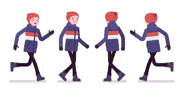 Молодой человек в полосатом пуховике идет и бегает, одетый в мягкую теплую зимнюю одежду